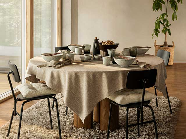 Breakfast table with clear doors and neutral tablecloth, chairs and flooring