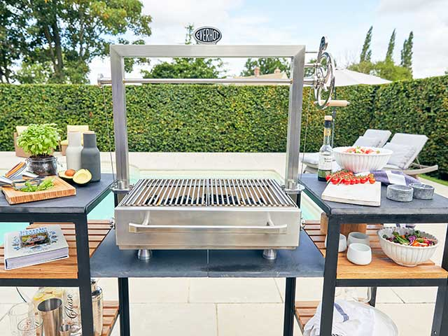 Outdoor cooking station on tiles with cookbook, salad, BBQ's and pizza ovens ready to go