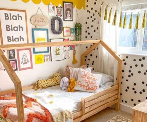 Colourful single bed with black and white polka dot wallpaper and frame wall