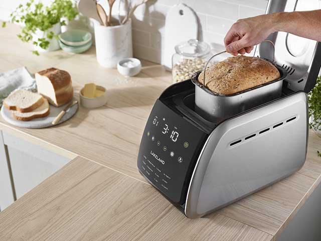 Bread makers on work top with fresh loaf in container