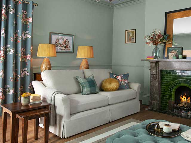 Cream sofa with open fireplace and Rosemore Laura Ashley AW21 eyelet curtains in background