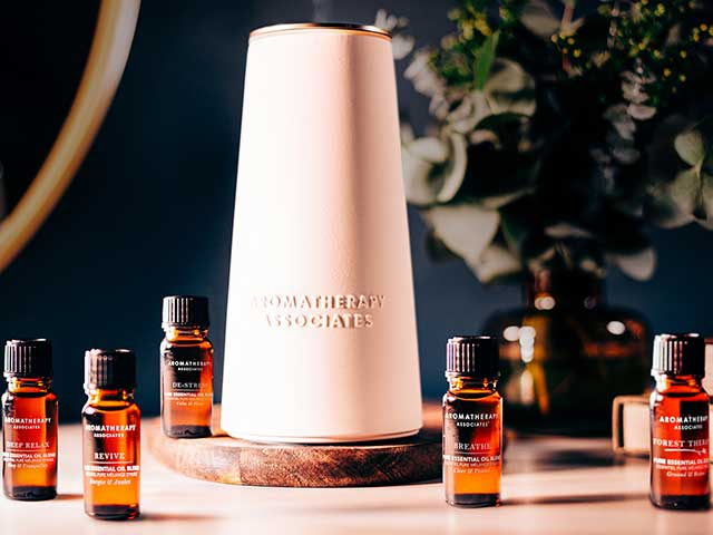 Aromatherapy Associates diffuser with essential oils on wooden surface